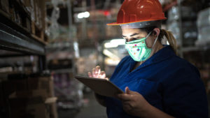 Maintenance worker in mask using tablet