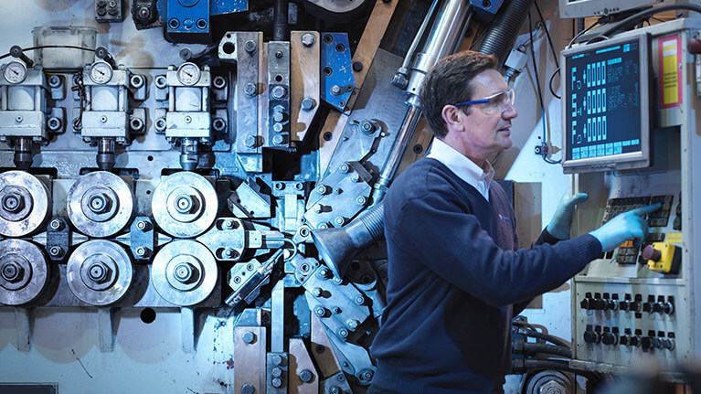man using controls in industrial manufacturing plant